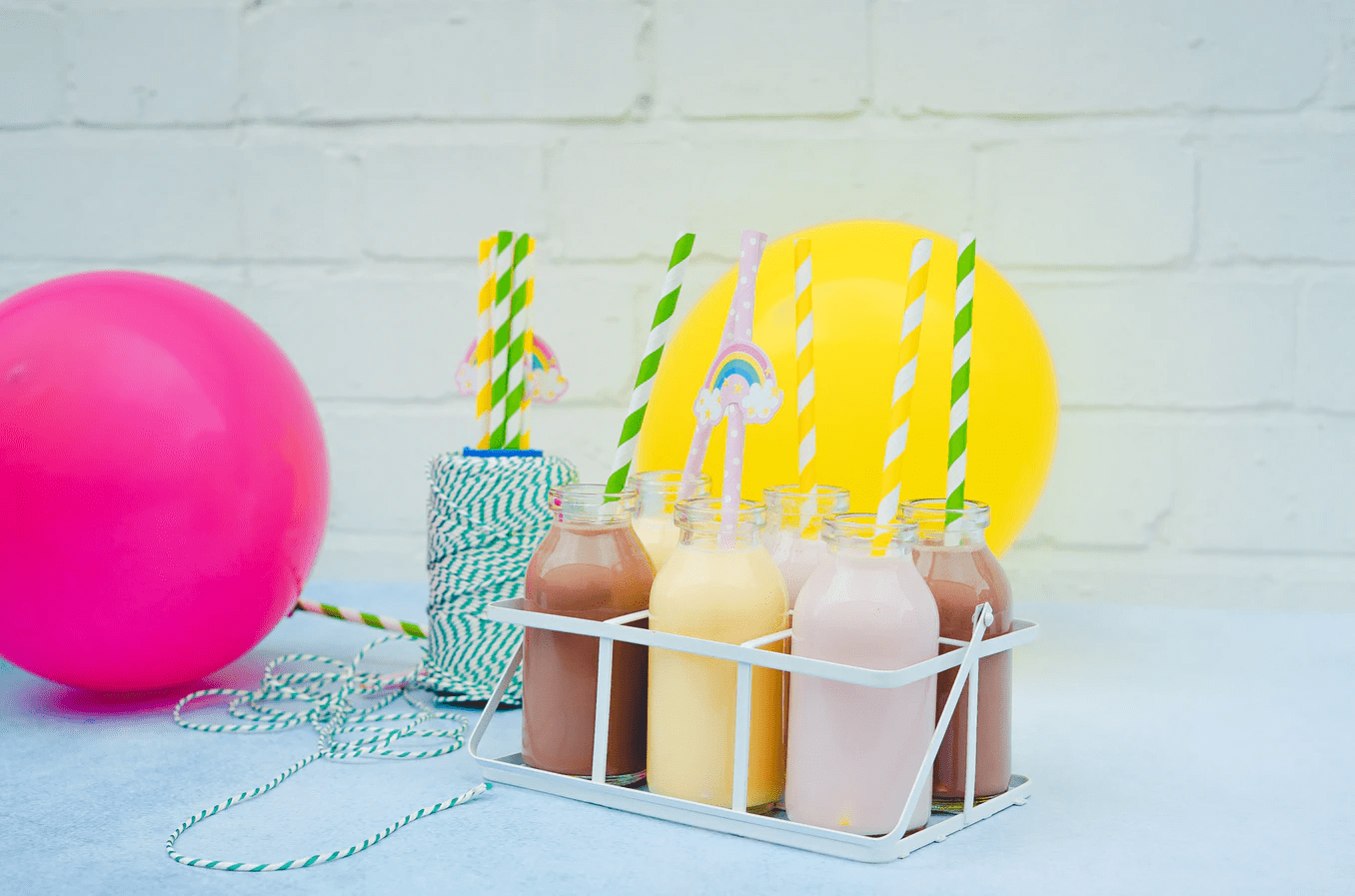 a pink balloon, a yellow balloon and 6 shakes
